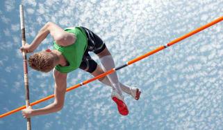 A pole vaulter clears a high bar