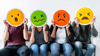 Four people holding up frustrated emoji faces
