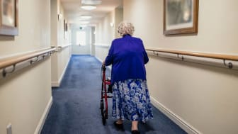 A lone senior woman walks down the hall of a retirement home pushing a wheelchair