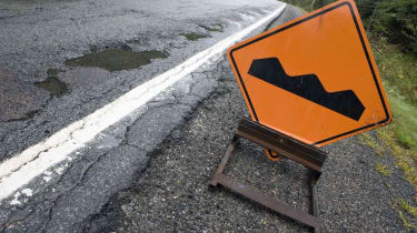 """A """"bump"""" sign sits beside a poor quality road."""