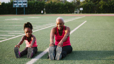 A mom and daughter stretch on a football field.