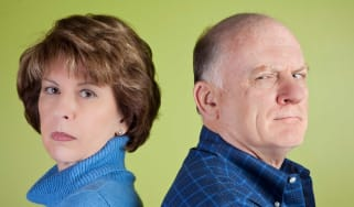A retired couple stand back to back with perturbed looks on their faces.