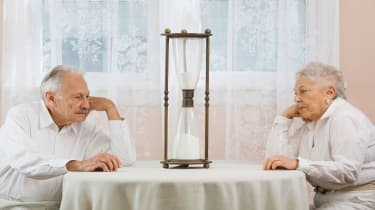 picture of elderly couple staring at an hourglass