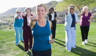 Senior Women taking exercise class outdoors in Arizona