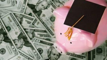 Pink piggy bank wearing college graduation cap sits atop scattered $20 bills