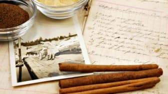 Collage of a vintage handwritten cookbook with cinnamon sticks, ginger, nutmeg, and an old photograph of a woman