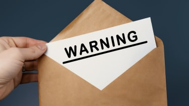 An envelop with a piece of paper with the word warning written on it.