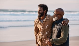 A young man walks with his gray-bearded dad on a beach