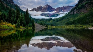 A view of the Rocky Mountains in Colorado with the mountains reflected in a small lake