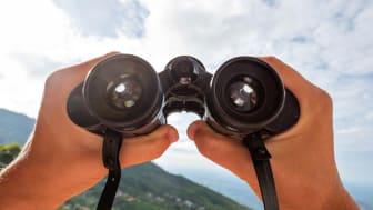 Binoculars focus on the horizon.