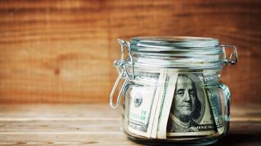 Dollar bills in glass jar on rustic table. Saving money concept.