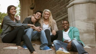 picture of four college students hanging out on some steps