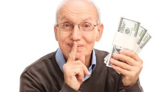 picture of elderly man holding money and making a shush sign