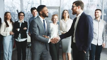 CEO shaking hands with new employee in front of other employees