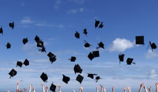 Students throw their graduation caps into the air