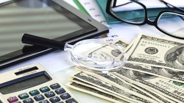 Pile of cash, a laptop, eyeglasses and paperwork on a desktop