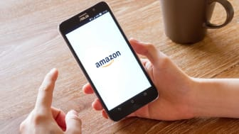 A shopper holding a phone opening the Amazon app