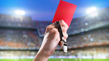 A soccer referee holds up a red card penalty.