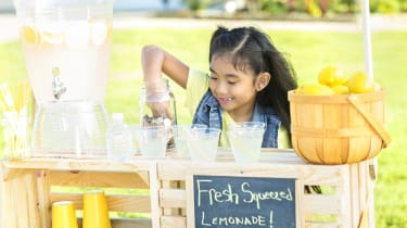 Happy girl makes fresh lemonade to sell at lemonade stand in her front yard. A basket of lemons and a beverage dispenser are on the stand.