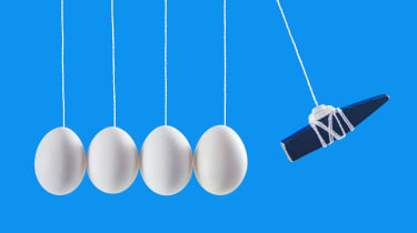 Several eggs suspended on ropes in a straight line with a weight poised to smash into them.