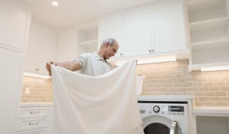 Senior man folding sheets in laundry room