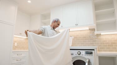 Senior man folding sheets in laundry room