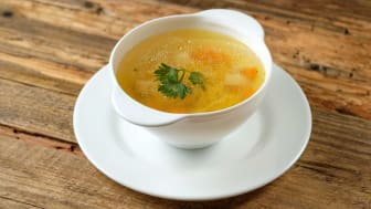A cup of chicken soup atop a platter on a tabletop