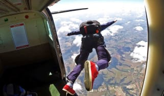 Man with parachute jumping out of a plane