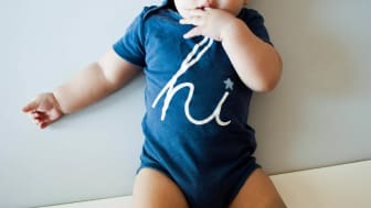 A baby boy is wearing a blue shirt with word hi on it while lying against white background