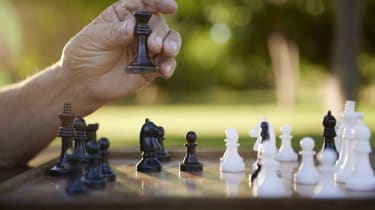 Active retired persons, hand of old man holding chess piece in park. Closeup shot, copy space
