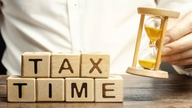 """picture of man putting an hourglass next to lettered blocks that spell out """"tax time"""""""