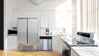 sunlit kitchen interior showing microwave refrigerator, stove and dishwasher