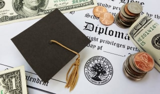 Graduation cap and money sitting on top of a diploma