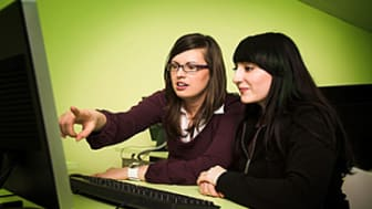 two women at computer clasroom looking in monitor