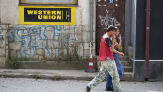 Two men walk past a Western Union sign outside a business building in Pristina, Kosovo. Western Union works with local agents to facilitate transferring money internationally. It operates in