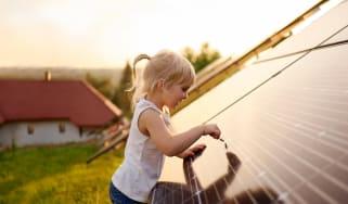 A little girl examines a solar panel.