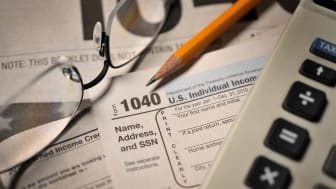 """Accountant's view of filing annual taxes; selective focus on numerals """"1040"""" and pencil point."""