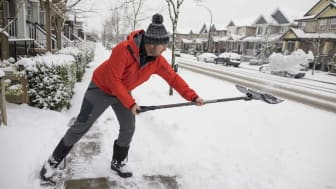 Side view shot of man shoveling snow off sidewalk in winter in suburb