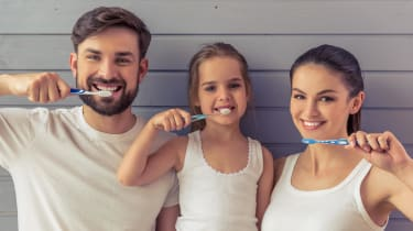 Parents and a small child brush their teeth together.