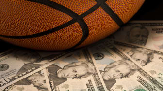 picture of a basketball sitting on money