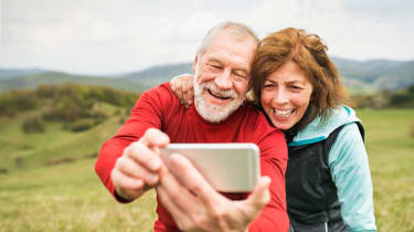 Older couple takes a selfie while out hiking in the mountains