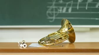 Music classroom, french horn on table in front of blackboard