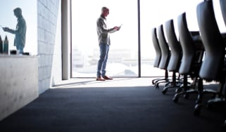 A man stands alone in a boardroom