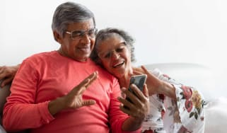 Senior couple chatting by video conference using a smart phone