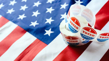 A roll of I Voted stickers sits, lightly unfurled, atop an American flag