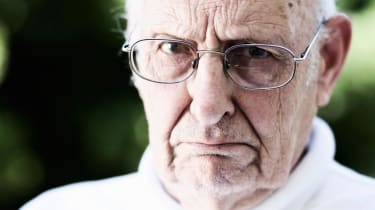 A very grouchy-looking older man glowers.