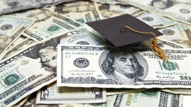 Graduation cap sitting on top of U.S. $100 bills and $20 bills