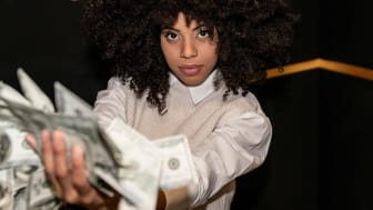 Woman in bank vault holds a handful of cash