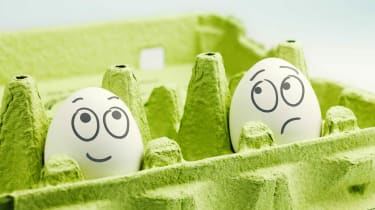 Two eggs in an egg carton: One with a happy face drawn on and one with a sad face.