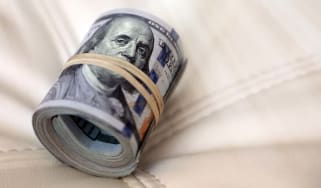 conceptual business and finance image of close up rubber banded and rolled up American one hundred dollar bills